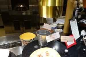 シェラトン・グランデ・トーキョーベイ・ホテルのYA-SHOKU(夜食)では、テーブルにあるバッジをカウンターに持っていってオーダーします。ピザの場合は写真中央の小さなバケツに入れます。